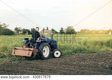 A Farmer Is Driving A Tractor Across The Field. Mill Grinding Machine For Soil. Land Cultivation. Re