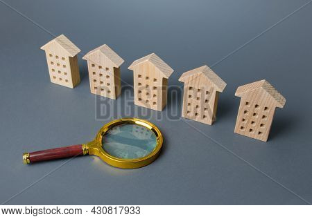 A Row Of Identical Houses And A Magnifying Glass. Apartment Search Concept. Buying Or Renting Housin