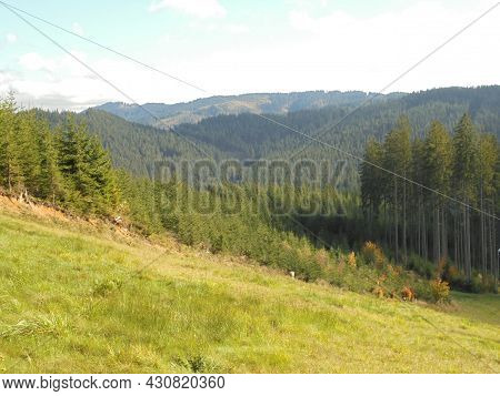 Mountainous Landscape In Beskydy. Hills Covered By Forests With Meadow In The Foreground. Panoramic