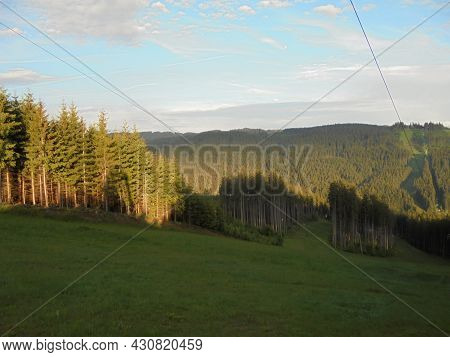 Mountainous landscape during sunset. Hills covered by fresh coniferous tree forests under dusk light. Panoramic image of Beskydy nature.