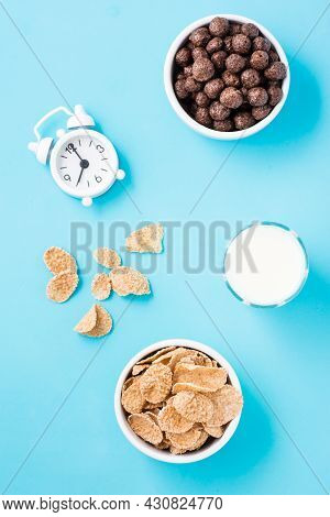 Bowls With Cereal Flakes And Chocolate Balls, A Glass Of Milk And An Alarm Clock On A Blue Backgroun