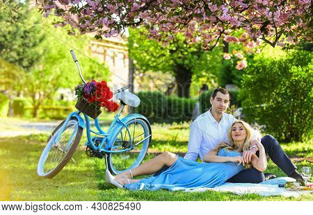 Arrived By Bike. Long Lasting Relationship. Couple Having Picnic In Park. Blooming Garden. Perfect S
