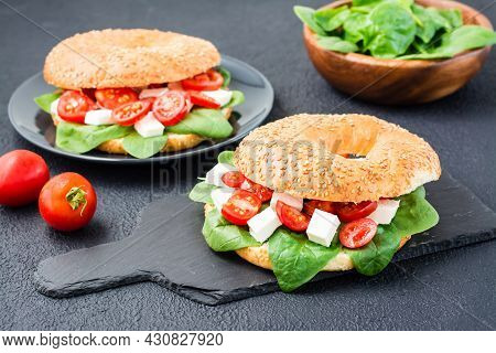 Delicious Ready-to-eat Bagels Stuffed With Tomatoes, Feta And Spinach Leaves On A Slate Board On A B