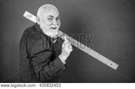 Education And Knowledge. Geometric Shapes At High School. Senior Man Teacher Use Ruler While Drawing