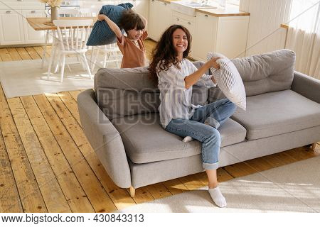 Young Mother Happy Laugh Playing With Small Preschool Son At Home. Cheerful Female Mom Or Nanny Enjo