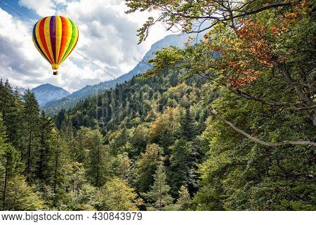 View Of High Apls Mountains Wth A Hot Air Balloon In The Blue Sky.