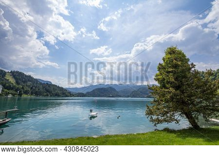 Panorama Of The Bled Lake, Blejsko Jezero, With Its Blue Waters During A Sunny Summer. Lake Bled Is