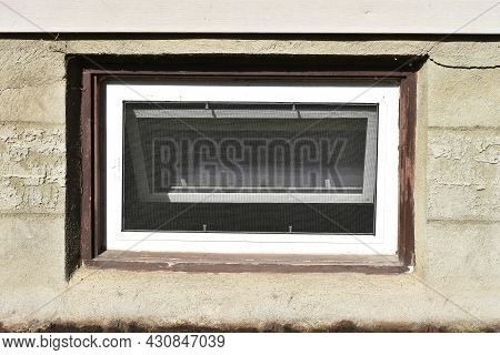 An Image Of An Old Basement Window With Brown Painted Trim.