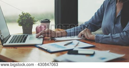 Businesswoman Checking Reported Profits On The Paper And Laptop.