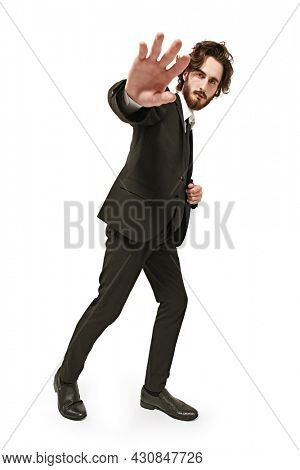 Fashion shot. Full length portrait of a handsome well-groomed man fashion model posing in motion at studio. White background with copy space.