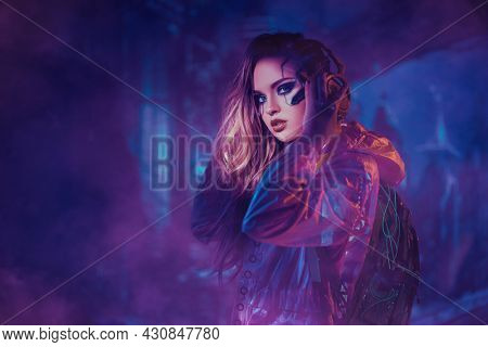 Cyberpunk concept. Portrait of an attractive cyberpunk girl in hi-tech clothes standing in the neon lights of the night city. Game, virtual reality.