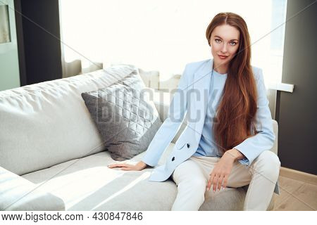 Attractive redhead girl poses on a sofa in her living room and smiling. Happy people and lifestyle concept.