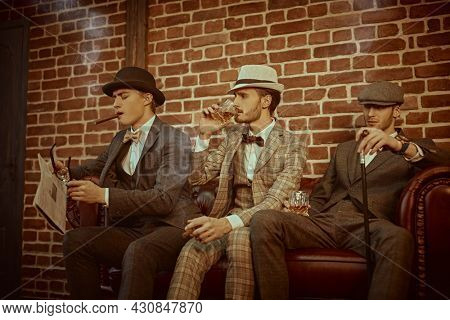 Three handsome men in elegant clothing spend time in loft interior of the club. Business people club. Men's fashion.
