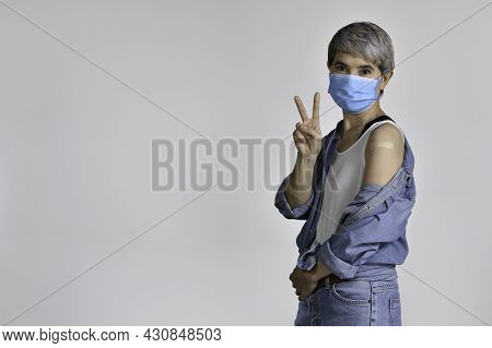 Happy Middle Aged Asian Woman Wearing Surgical Mask For Corona Virus And Vaccinated Smiling With Hap