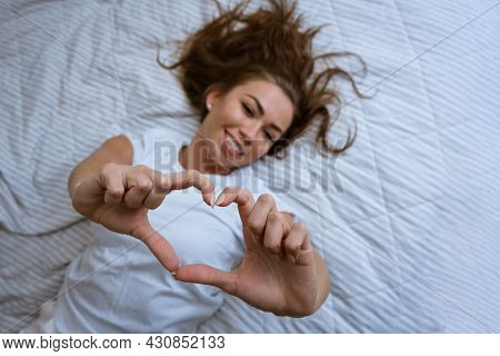 Happy Young Woman Wake Up In Comfortable White Bed, Welcomes A New Sunny Day, Smiling Woman Wake Up