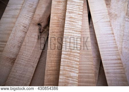 Curly maple or flame maple, tiger maple a sought after and prized wood for its beautiful figured grain. Wood working lumber on work bench.