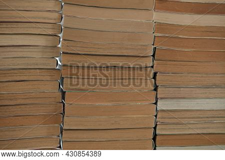 Old books, stacked up. Sides of old  books in three stacks.