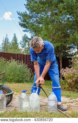 Man In A Blue Jumpsuit Pours Drinking Water From A Hose Into Large Bottles. Eco-friendly Drinking Wa