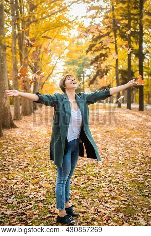Middle-aged Woman Walks, Throwing Orange Leaves In The Autumn Park. Active Lifestyle, Happy Pension.