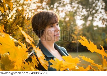 Middle-aged Woman Walks In The Autumn Park. Orange, Red Leaves. Active Lifestyle.