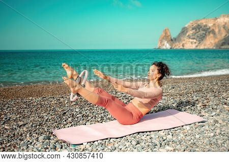 Young Woman With Black Hair, Fitness Instructor In Pink Sports Leggings And Tops, Doing Pilates On Y