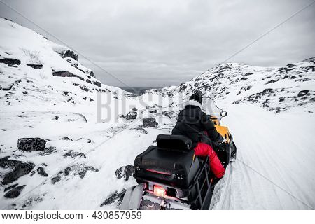 A Man Is Riding Snowmobile In Mountains. Beautiful Morning Light. A Winter Ride On A Snowmobiles, Wi