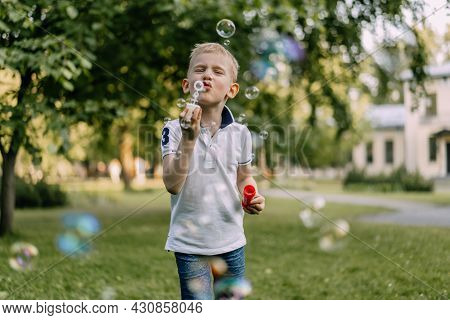 Cute Caucasian Blond Boy Blowing Soap Bubbles In Park. High Quality Photo