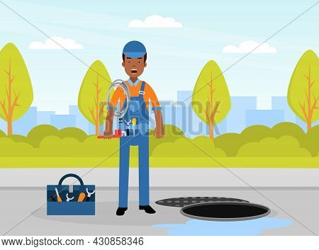 Man Plumber Wearing Blue Overall Holding Hosepipe Standing Near Manhole Engaged In Fixing Tubes And