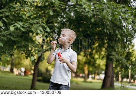 Cute Caucasian Blond Boy Blowing Soap Bubbles In Park