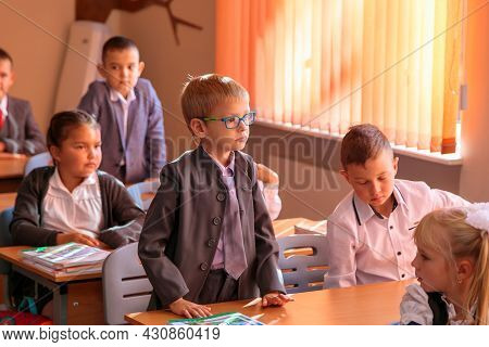 The First Grader Stands At The Desk And Answers The Teacher's Question.
