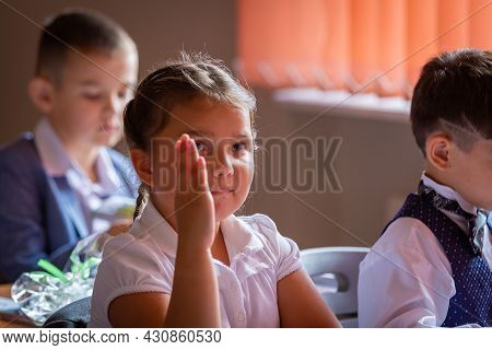 The First Grader Sits At Her Desk With Her Hand Raised, Wants To Answer The Teacher.