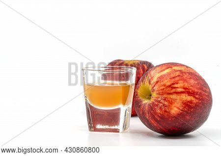 Small Shot Glass Of Organic Apple Cider Vinegar With The Mother, Two Red Apples Is Aside Of The Glas