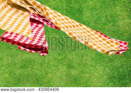Picnic Background. Red And A Yellow Checkered Picnic Cloth On Blurred Sun-flooded Lush Grass With Fo