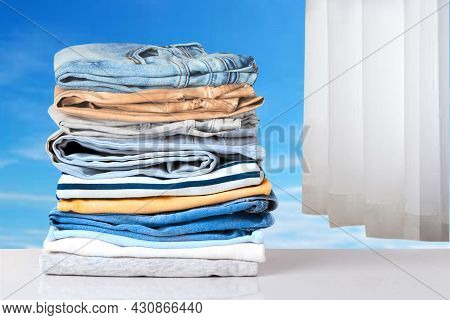 Stack Of Jeans. Closeup Of A Pile Of Colorful Denim Pants And Colorful Sweater On A Bright Table Aga