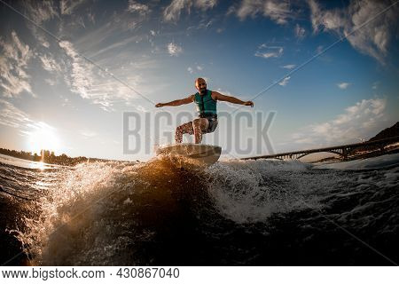 Energetic Sports Man Riding On Wakeboard Down The River Waves Against The Blue Sky And Bridge