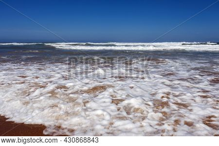 Sandy Beach With Long Waves And White Foam On The Southern Coast Of The Ocean. Sea Beach And  Turquo