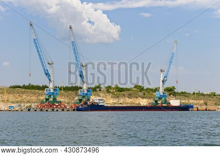 Cargo Port Cranes Load A Sea Barge On A Sunny Summer Day