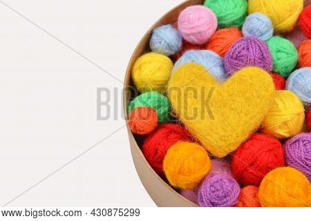 A Lot Of Multi-colored Wool Balls Of Yarn With A Yellow Wool Heart In A Round Cardboard Box On A Whi