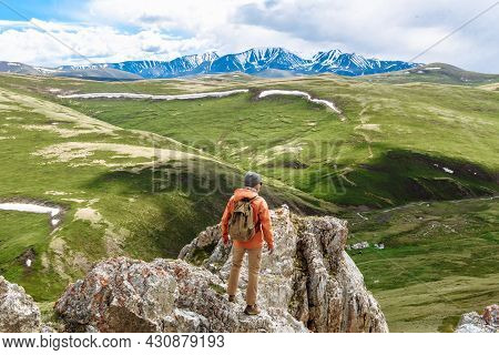 Hiker Man Or Climber With A Backpack Stands On The Top Of The Mountain And Looks At The Valley Of Th