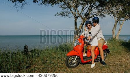 Scooter Road Trip. Love Couple On Red Motorbike In White Clothes On Forest Road Trail. Just Married