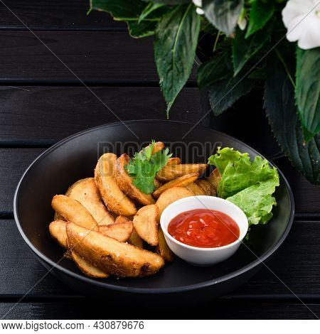 Chips Fried Potatoes. Food In A Plate On A Dark Black Table Background.