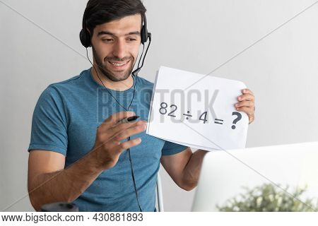 Education Online. Handsome Man Teacher With Headset Showing Blank Paper Sheet For Teaching Online At