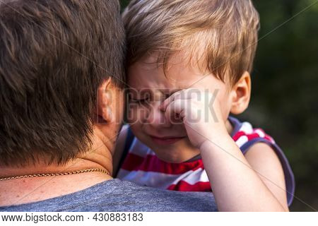 A Little Boy Is Crying While Being In His Father's Arms, Snuggling Up To Him To Feel Protected.