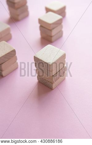 Set Of Stacks Of Wooden Cubes On Pink Background