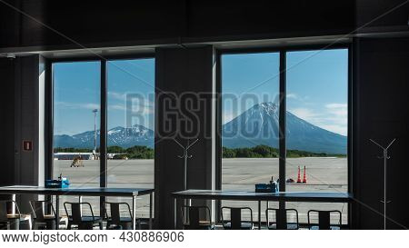 Conical Volcanoes Against The Blue Sky Are Visible Through The Airport Windows. There Is Snow On The