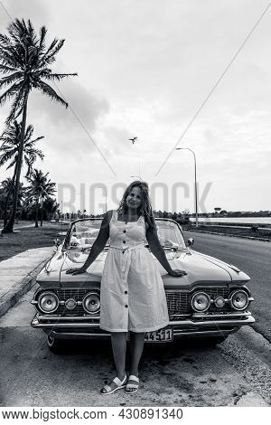 Varadero, Cuba - May 20, 2021: Oldsmobile Super 88 1959 In Cuba. Young Woman On The Hood Of A Conver