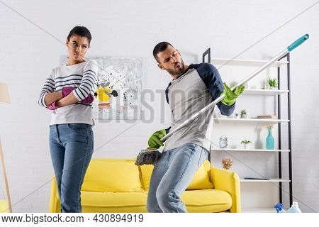 Man Playing On Mop Near Offended African American Girlfriend In Rubber Gloves