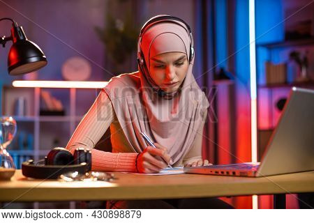 Pleasant Focused Confident 25-aged Arabian Woman In Headscarf And Headset, Making Notes While Listen