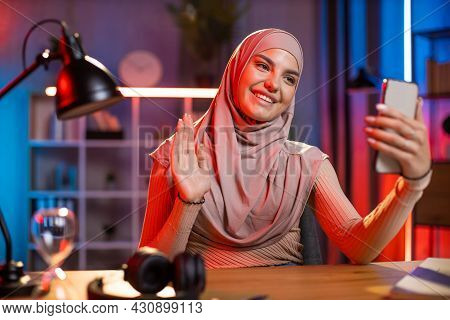 Pretty Smiling Arabian Woman Using Modern Cell Phone For Making Video Call, Waving To Her Friend. Po
