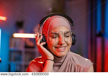 Close Up Portrait Of Pretty Smiling Happy Relaxed 30-aged Arabian Woman In Hijab In Headphones Liste